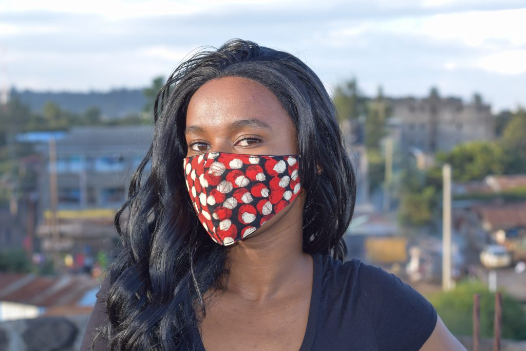 Jeune femme portant un masque en tissu africain - ADAKAD